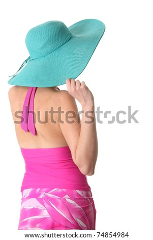 Lady wearing a pink tankini and a turquoise sun hat. - stock photo