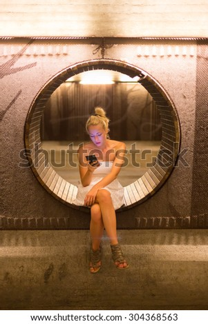 Lady wearing white summer dress playing carelessly with her android smart phone browsing trough social networks while waiting on contemporary circular bench in urban pedestrian underpass. - stock photo