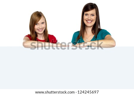 Lady with daughter posing behind blank billboard isolated against white. - stock photo