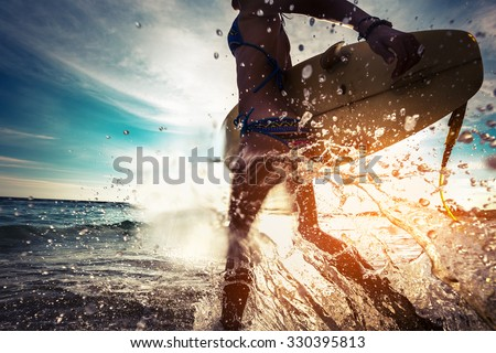 Lady with surfboard running into the sea with lots of splashes - stock photo