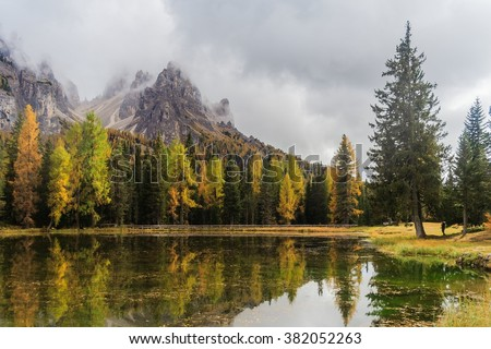 Lago Antorno with mauntain reflected in the lake and trees in autumn colours - stock photo
