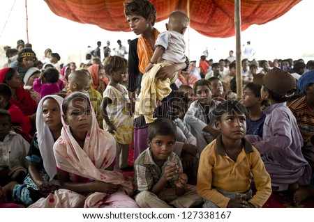 LAHORE, PAKISTAN- AUG 2: Unidentified children in brick kiln wait for the food from relief team on August 2 2012 in Lahore, Pakistan. Children in Pakistan suffer from malnutrition. - stock photo