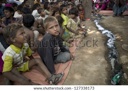 LAHORE, PAKISTAN- AUG 2 : Unidentified children in brick kiln wait for the food from relief team on August 2 2012 in Lahore, Pakistan. Children in Pakistan suffer from malnutrition. - stock photo
