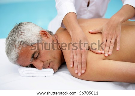 Laid man being massaged - stock photo