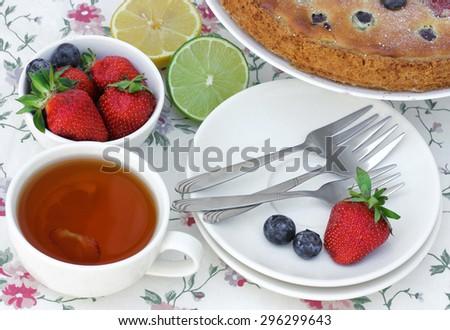 Laid table dessert: cake, tea, fresh berries - stock photo