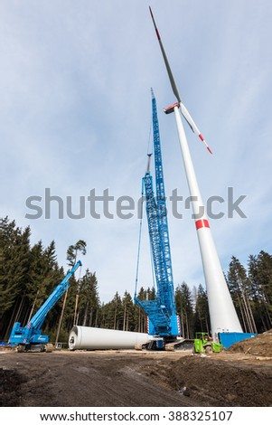 LAIMERING, GERMANY - FEBRUARY 27, 2016: Construction of a wind turbine with large crane and other heavy machinery in wood glade near Laimering in Bavaria, Germany. - stock photo