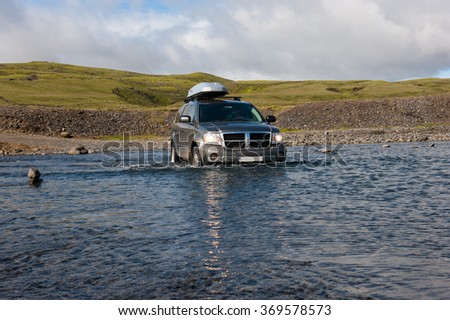 LAKAGIGAR, ICELAND - AUGUST 27, 2012: Off road driving in Iceland. Dirty Jeep Dodge Durango crossing the river on the way to Laki Craters. Lakagigar is a volcanic fissure in the south of Iceland. - stock photo