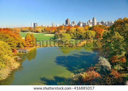 Lake and Autumn foliage with apartment buildings in Central Park of midtown Manhattan New York City - stock photo