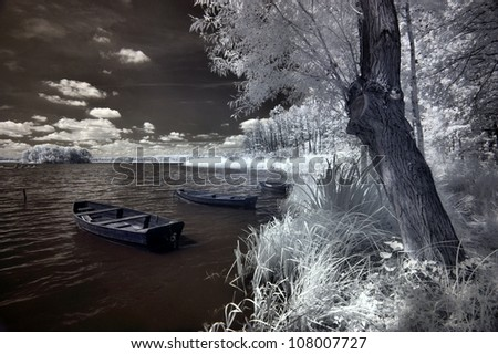 Lake and boats in Greater Poland, Poland. The infrared image - stock photo