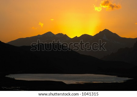 Lake and mountain silhouette on sunset - stock photo