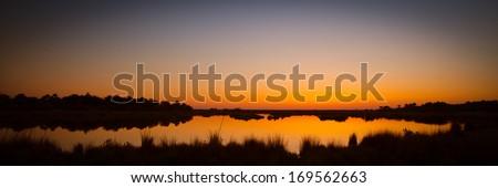 Lake at sunset, Black Point Wildlife Drive, Merritt Island National Wildlife Refuge, Titusville, Florida, USA - stock photo