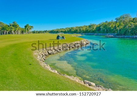 Lake at the beautiful golf course with the cart at the back. Mexican resort. Bahia Principe, Riviera Maya. - stock photo