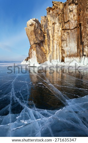 Lake Baikal. Beautiful cliffs reflected in the smooth surface of the ice. Sunset light - stock photo