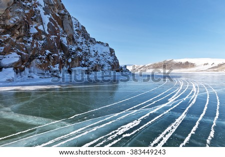 Lake Baikal in winter. Traces of the snowmobile on the smooth ice. Winter travel on the frozen lake - stock photo