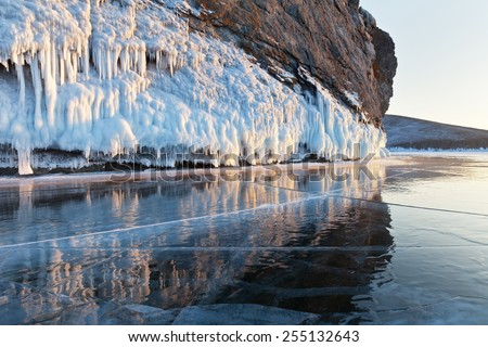 Lake Baikal. Reflection of rocks in the mirrored surface of ice evening in February - stock photo