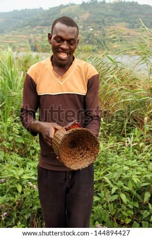 LAKE BUNYONI, UGANDA - CIRCA SEPTEMBER 2012. A Ugandan man displays a crayfish on a wicker crayfishing trap on the shores of Lake Bunyoni during September 2012. - stock photo