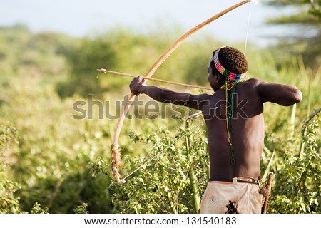 LAKE EYASI, TANZANIA - FEBRUARY 18: An unidentified Hadzabe bushman with bow and arrow during hunting on February 18, 2013 in Tanzania. Hadzabe tribe threatened by extinction. - stock photo