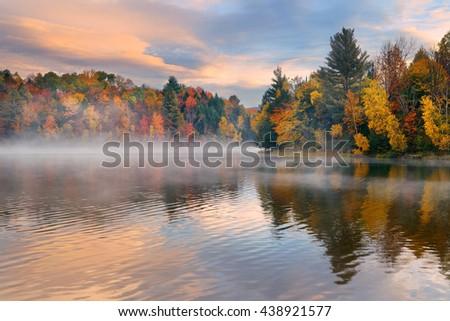 Lake fog sunrise with Autumn foliage and mountains in New England Stowe - stock photo