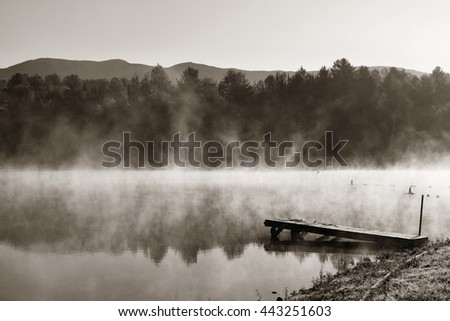 Lake fog with Autumn foliage and mountains with reflection in New England Stowe - stock photo