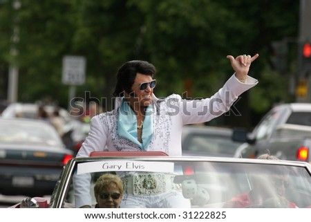 LAKE GEORGE, NY - MAY 30 : An Elvis impersonator rides in the Elvis Classic Car Parade during the 2009 Lake George Elvis Festival May 30, 2009 in Lake George, NY. - stock photo