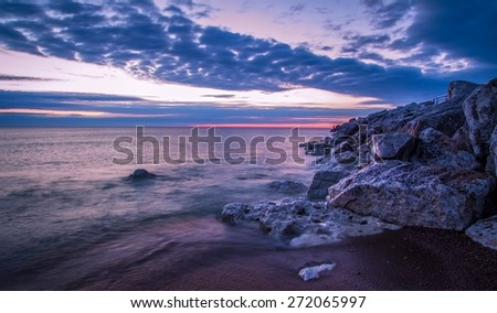 Lake Huron Sunrise. Wave crashes over the rocky Lake Huron coast. Tierney Park. Lexington, Michigan. - stock photo