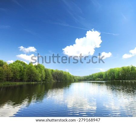 lake in silent summer day with reflections of clouds  - stock photo