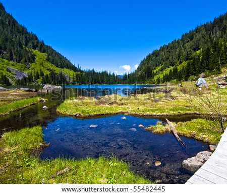 Lake 22 is an alpine lake in western Washington. It is a beautiful hike with views of far off snow covered mountain peaks and green hills. - stock photo