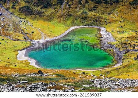 Lake like the heart.  Picture was taken during trekking hike in the beautiful and scenic Caucasus mountains at autumn, Arhiz region, Abishira-Ahuba range, Karachay-Cherkessia, Russia - stock photo