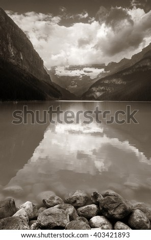 Lake Louise at sunrise with rocks in Banff national park with mountains and forest in Canada. - stock photo