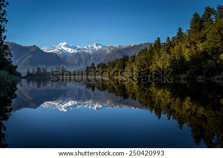 Lake Matheson. The reflection of sunrise over Mt.Cook through the lake. It is one of the most famous lake in West Coast next to Fox Glacier / New Zealand. - stock photo