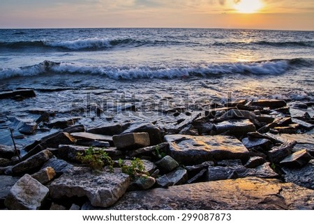 Lake Michigan Sunset. Rocky shore of Lake Michigan at sunset. - stock photo