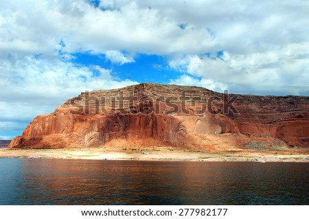 Lake Powell landscape includes huge sandstone formations along its shores. - stock photo