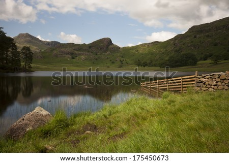 lake shore at blea tarn in cumbria on a lovely summers day overlooking the mountain range - stock photo
