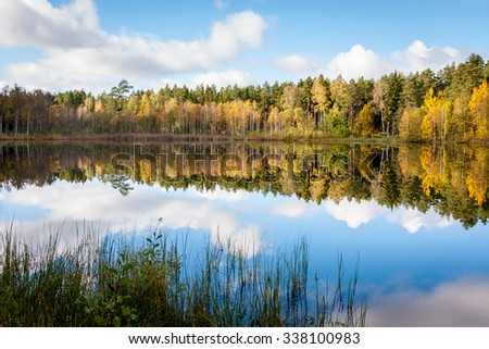 Lake surrounded by autumn colored trees with the reflection of trees and sky in the water - stock photo