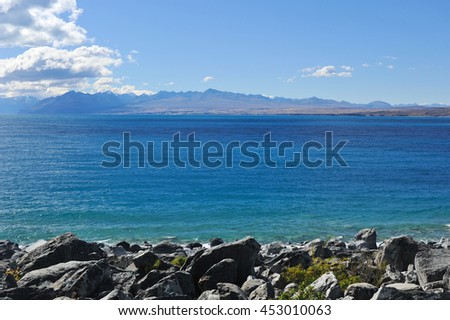 Lake Tekapo and beautiful rocks with the mountains background in sunny day - stock photo