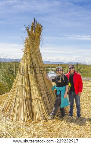 Lake Titicaca, Peru - Couple of tourists poses near reed bundle on one of floating islands - stock photo