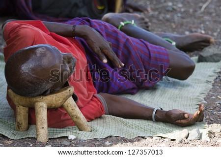 """LAKE TURKANA, KENYA - JANUARY 12: El molo man resting on traditional """"head rest"""". January 12 2013 at Lake Turkana - stock photo"""