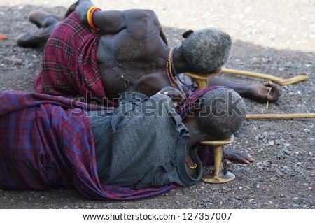 """LAKE TURKANA, KENYA - JANUARY 12: El molo men resting on traditional """"head rest"""". January 12 2013 at Lake Turkana - stock photo"""