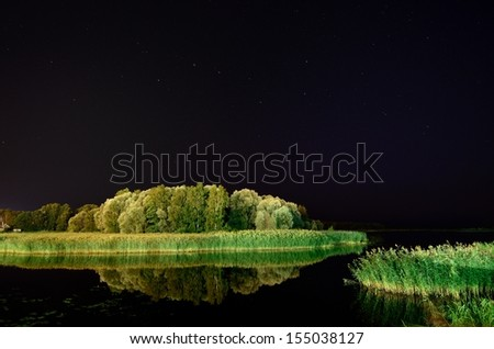 Lake under a clear sky by night - stock photo