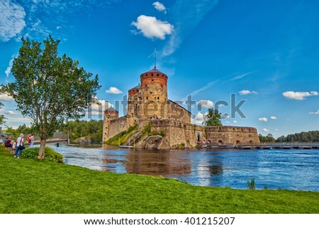 Lake view with grass and reflections of Olavinlinna Olofsborg, the 15th-century medieval three-tower castle located in Savonlinna, Finland. - stock photo