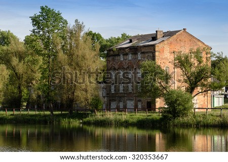 Lake with old abandoned house on right bank reflection in water - stock photo