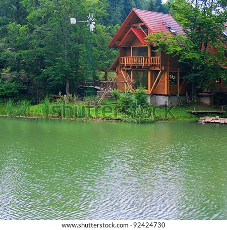Lake with the wooden house ashore in the summer - stock photo