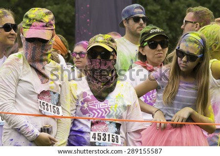 """LAKE ZURICH, ILLINOIS, USA - June 20, 2015: Two women wear caps, sunglasses and scarves in anticipation of blasts of colored powder at the start of a 5K """"fun run"""" in this suburb of Chicago. - stock photo"""