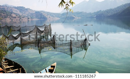 lakeside in Pokhara with the fishing net with mountain range - stock photo
