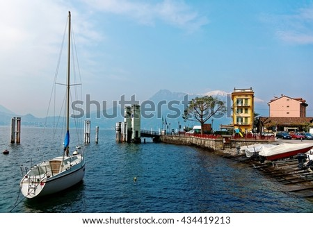 Lakeside scenery of Varenna in springtime, a beautiful village by Lake Como in Lombardy, Italy with a view of sailboats parking at the pier by lakeshore & snow capped mountains in distant background - stock photo
