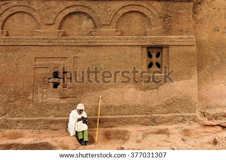 LALIBELA, ETHIOPIA - AUGUST 30: Ethiopian pilgrim by the wall of ancient church carve in solid rock in Lalibela, Ethiopia in Lalibela in August 30, 2013 - stock photo