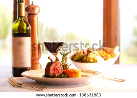 Lamb chops on a white plate with red wine. - stock photo