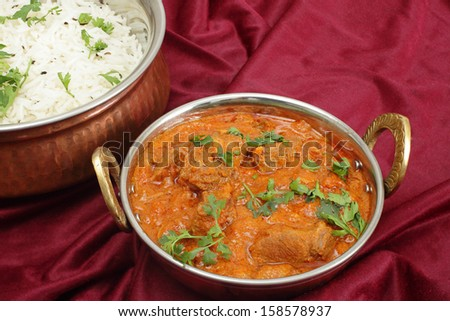 Lamb rogan josh, served with jeera (cumin) rice in beaten copper bowls. A tilt-shift lens has been used to achieve huge depth of field. - stock photo