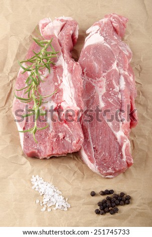 lamb shoulder chops with coarse salt, pepper and rosemary on brown kitchen paper  - stock photo