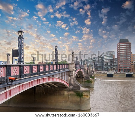 Lambeth Bridge, London. Beautiful red color and surrounding buildings at sunset. - stock photo